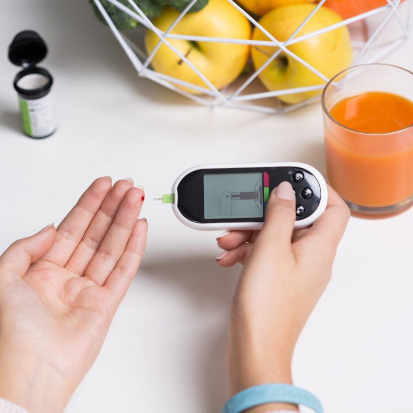 Woman with glucometer measuring blood sugar value