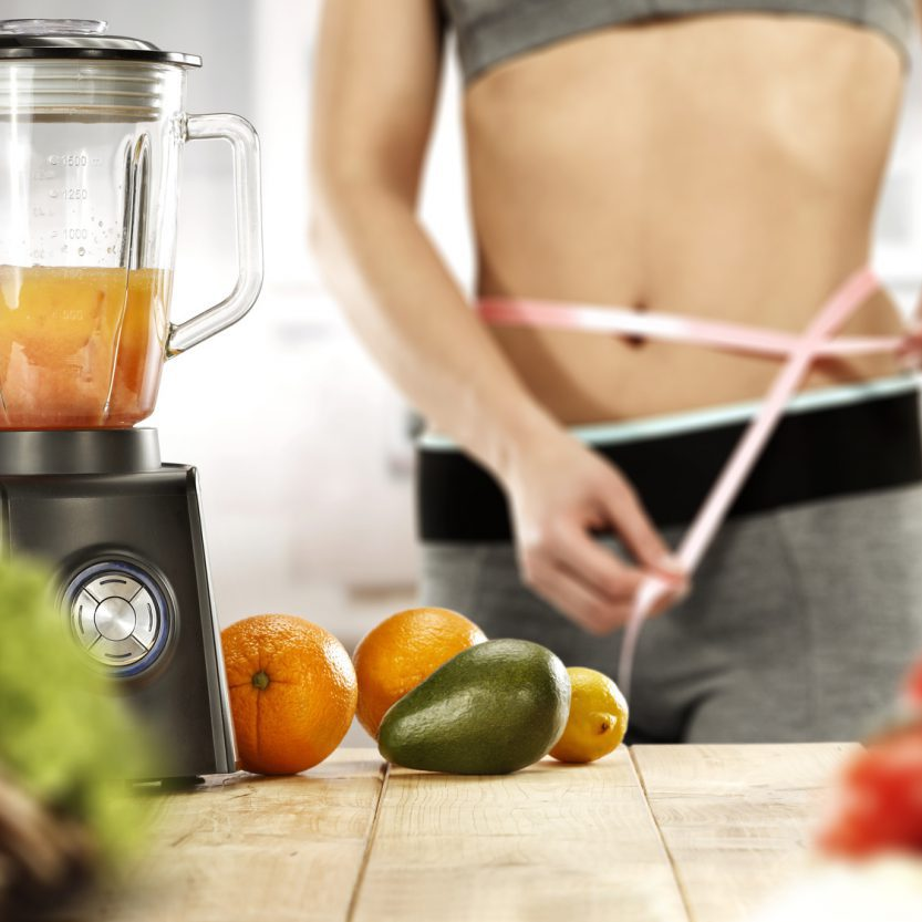 woman body in kitchen and blender on table